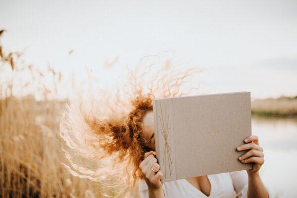 Kobieta tańczy z albumem beżowym na zdjęcia i macha włosami