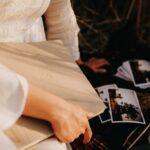 Kobieta wkleja zdjęcia do tradycyjnego albumu w kolorze kawy z mlekiem