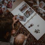 Tata z córeczką wklejają zdjęcia do albumu dla dziecka