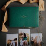 Zdjęcia rodzinne obok zielonego pudełka na zdjęcia z napisem rodzina