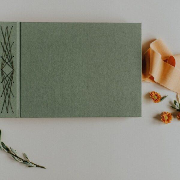 Zielony jednokolorowy album do wklejania zdjęć zawiązywany na złotą wstążkę