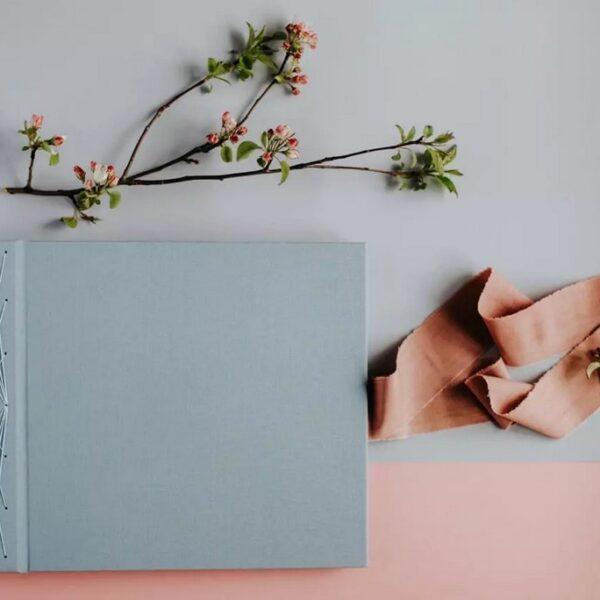 Jednokolorowy, błękitny album do wklejania zdjęć przewiązywany różową wstążką